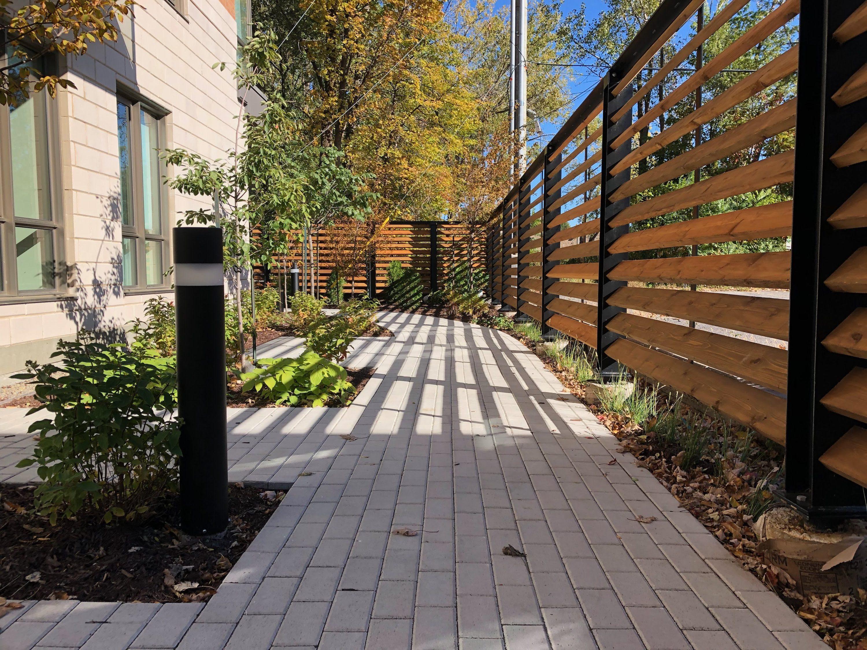 amenagement-paysager-residence-pour-aines-sentier-sinueux-en-pave-de-beton-plantation-d-arbres-a-petit-deployement-eclairage-paysager